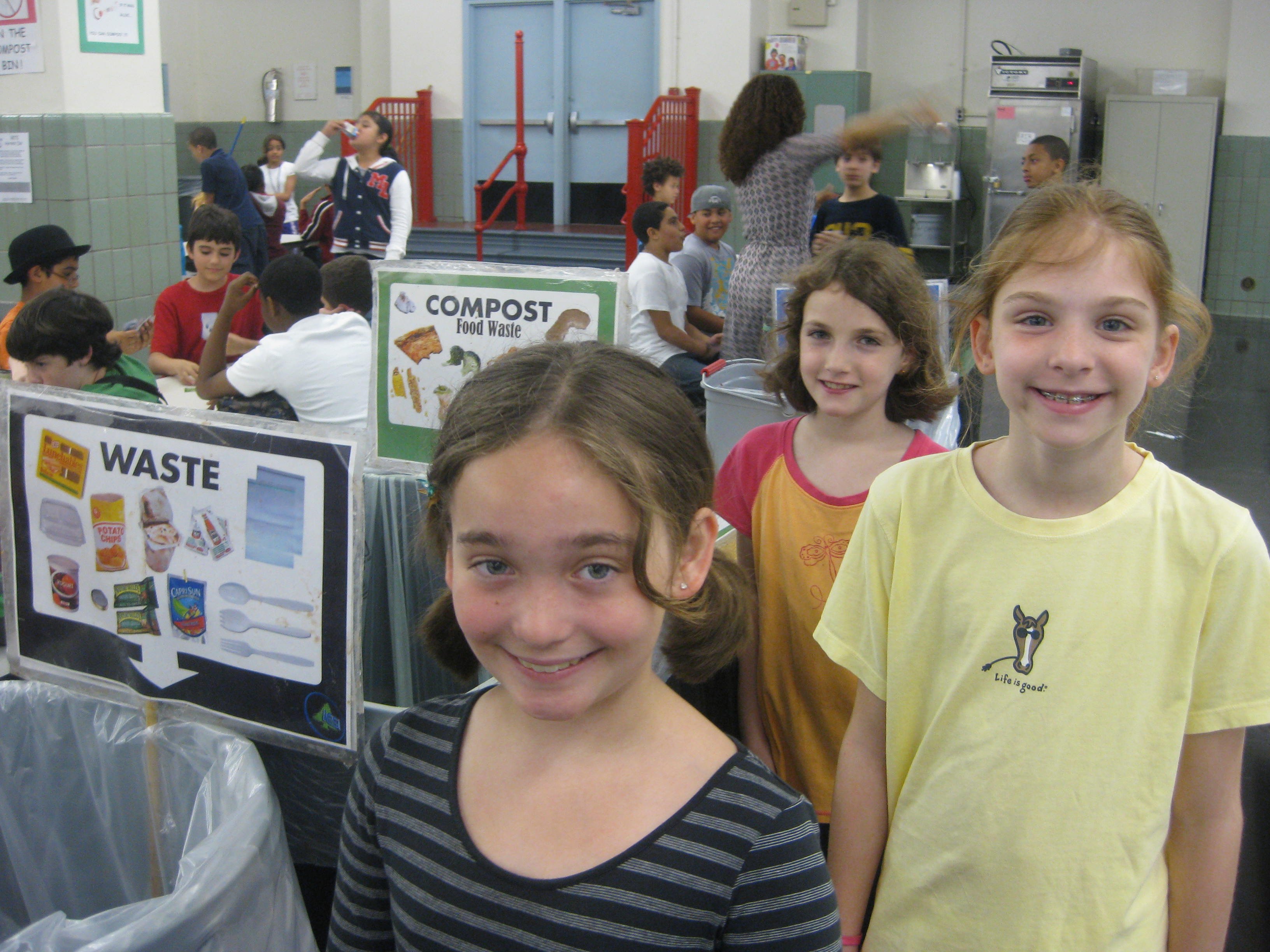 Student 'Green Team' members with cafeteria source separation set-up