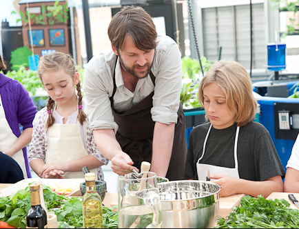 Students participating in a harvest/cooking demo. in their Hydroponic Greenhouse science lab